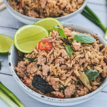 Fried rice in a grey bowl with lime and Thai basil