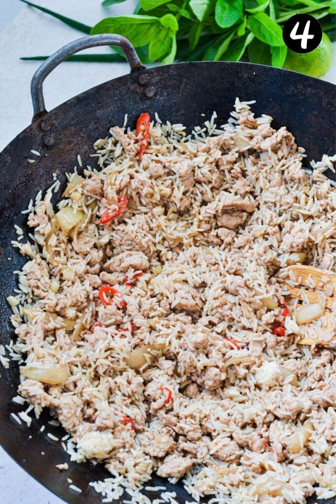 chicken and rice frying in a wok