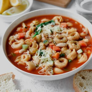 close up of tortellini soup with vegetables in a white bowl