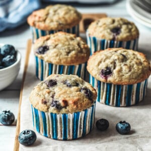 cupcakes arranged on a wooden board surrounded by blueberries.