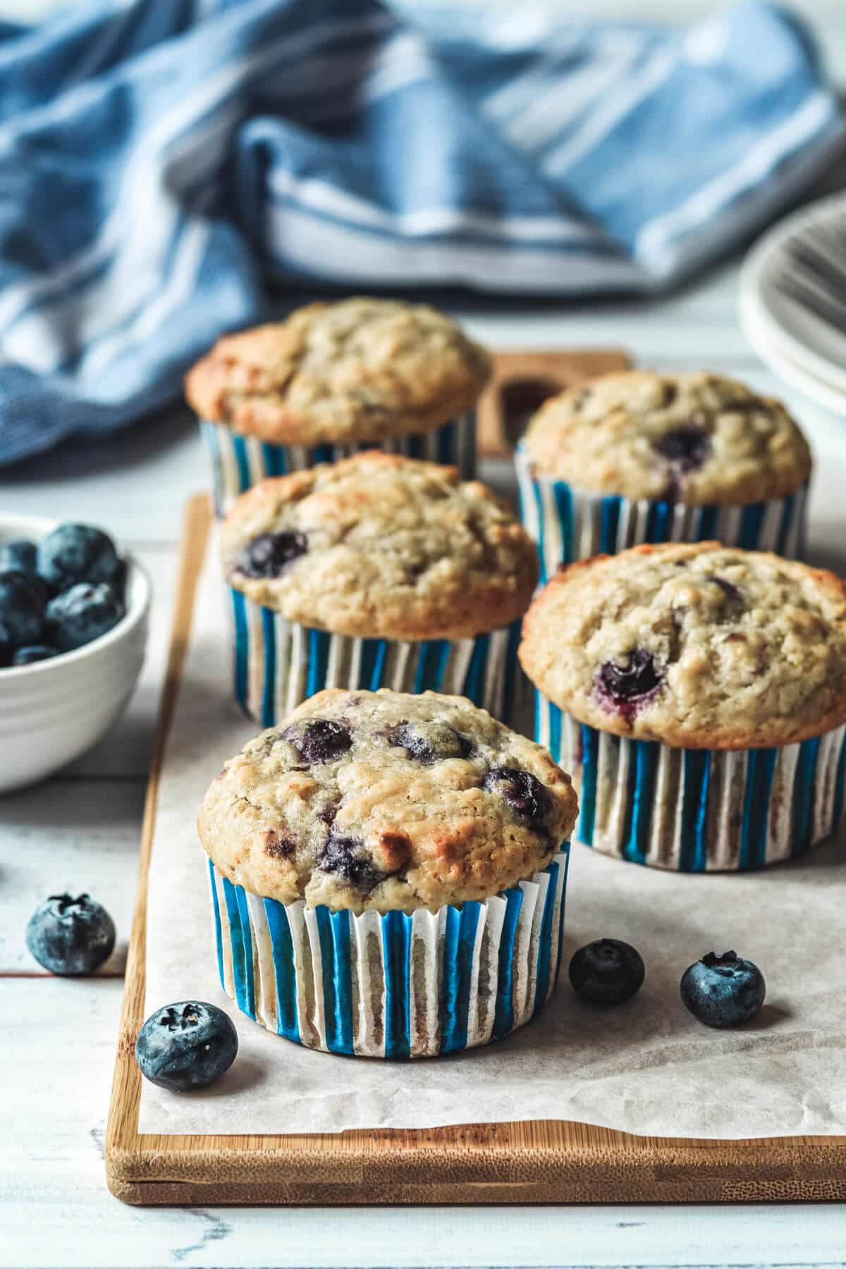 cupcakes arranged on a wooden board with blueberries
