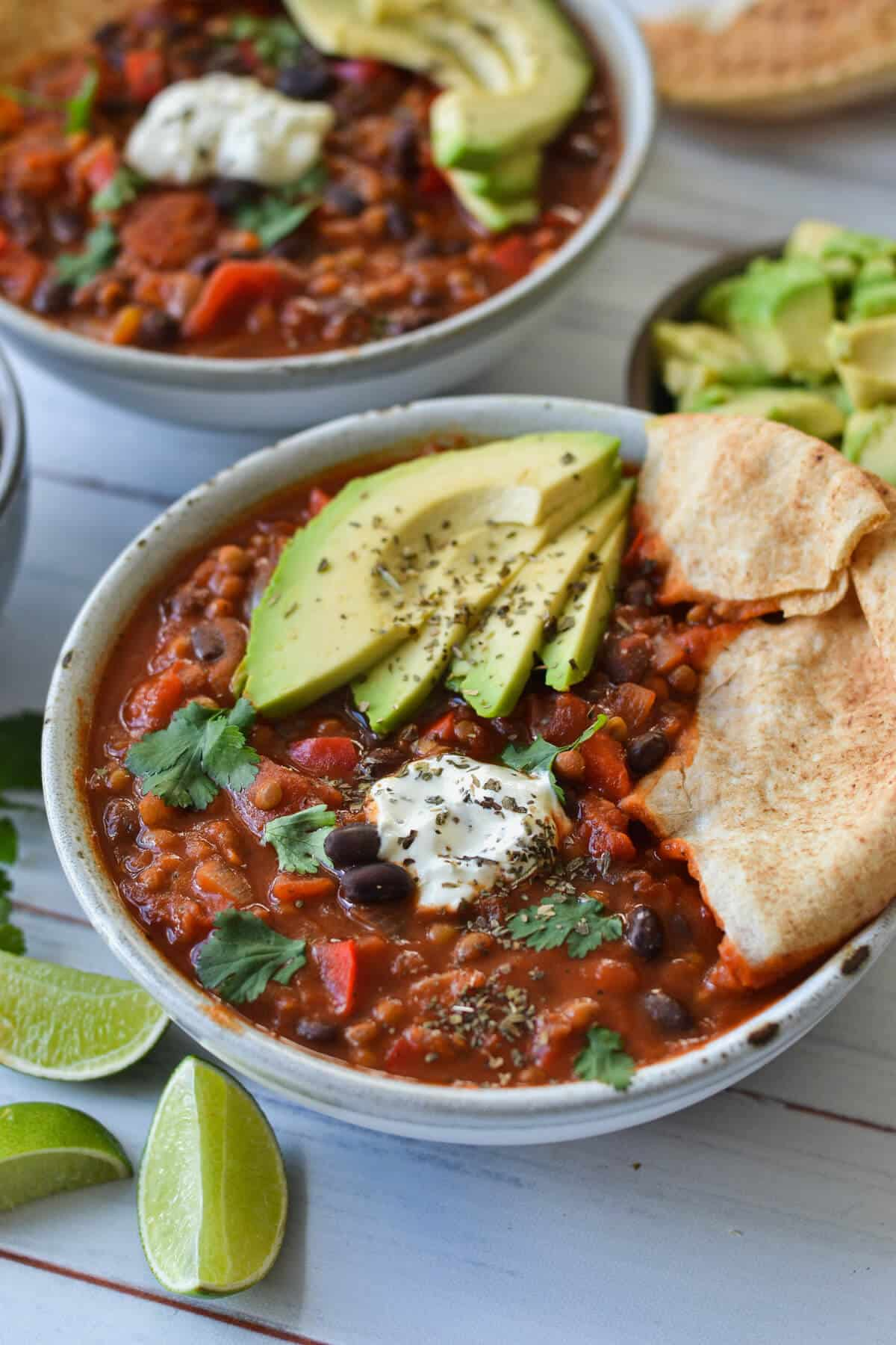 side view of vegetarian chilli in a grey bowl topped with pita bread and avocado.
