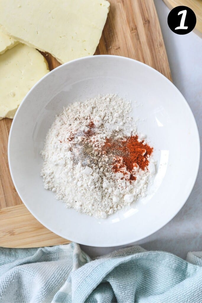 flour and paprika mixture in a white bowl.