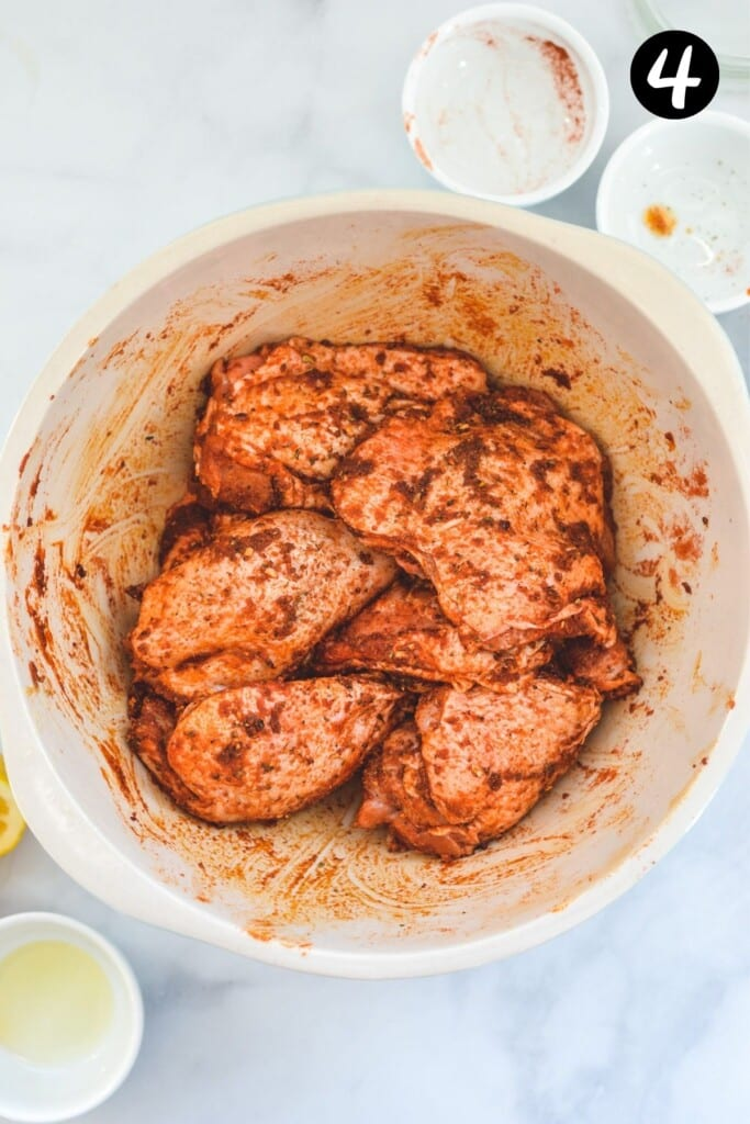 chicken pieces in a mixing bowl coated in spices
