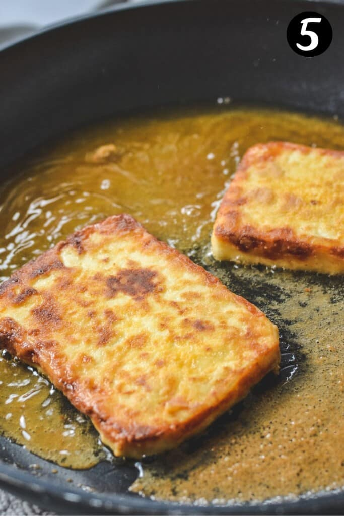 pieces of golden, fried halloumi in a pan with oil
