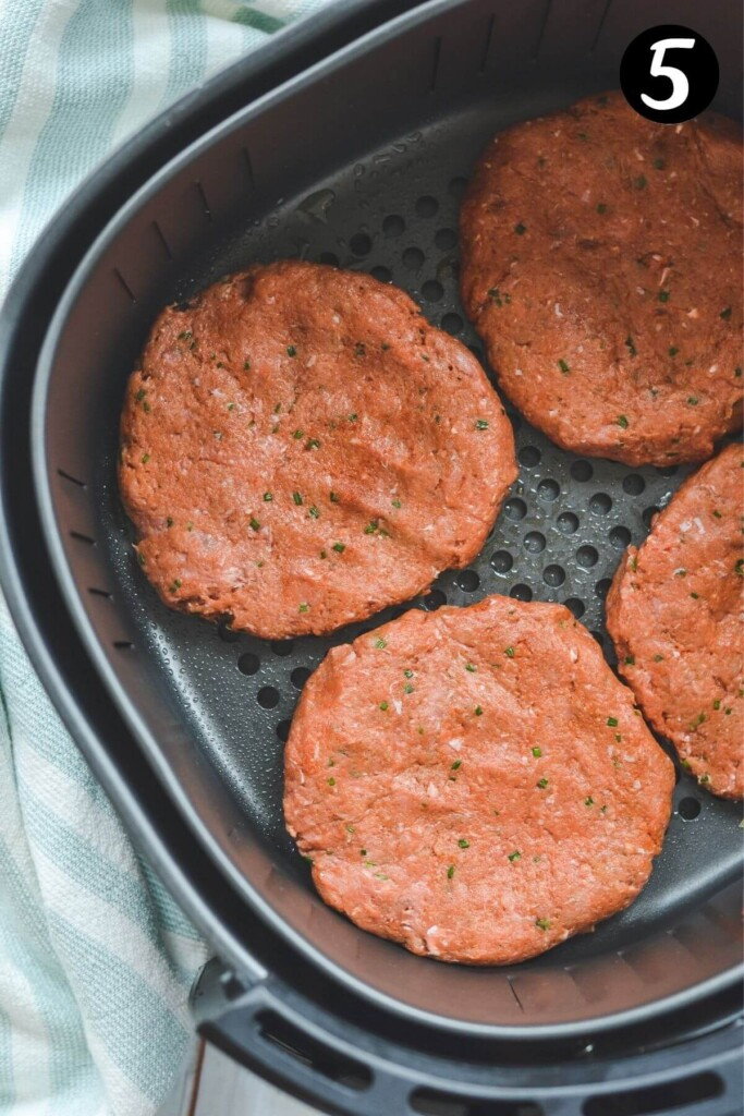 raw burger patties arranged in an air fryer basket.