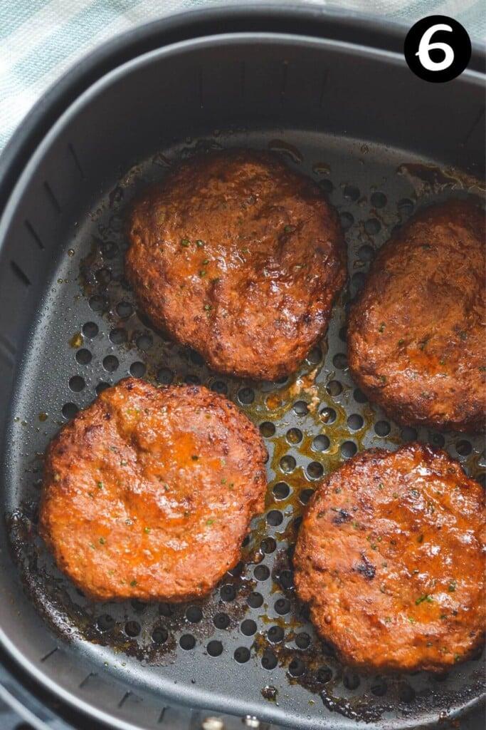 cooked turkey burger patties in an air fryer basket.
