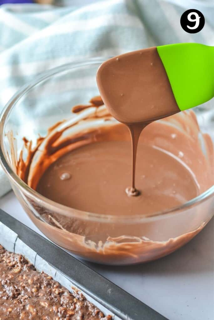 melted chocolate dropping from a green spatula over a glass bowl