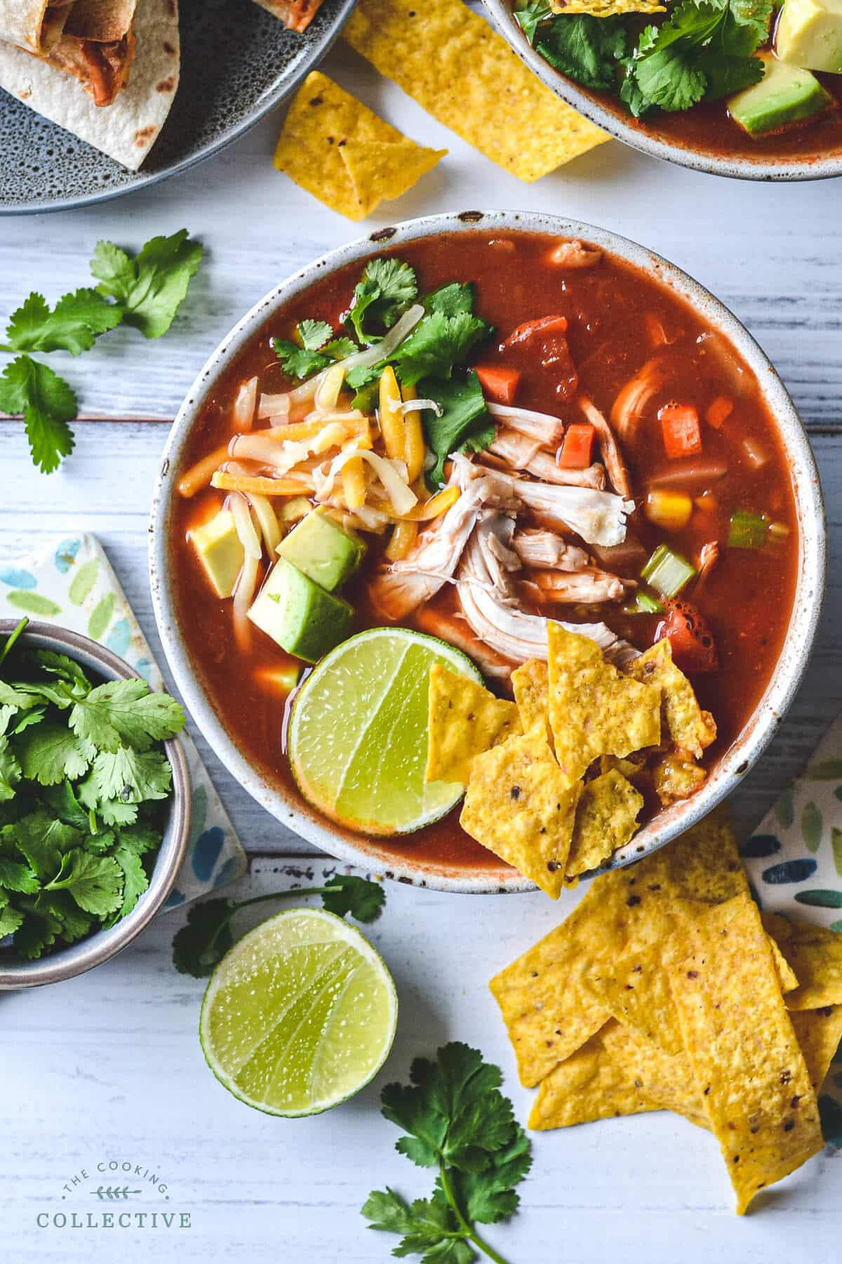 top view of a bowl of soup laid out on a table with tortilla chips, lime and coriander