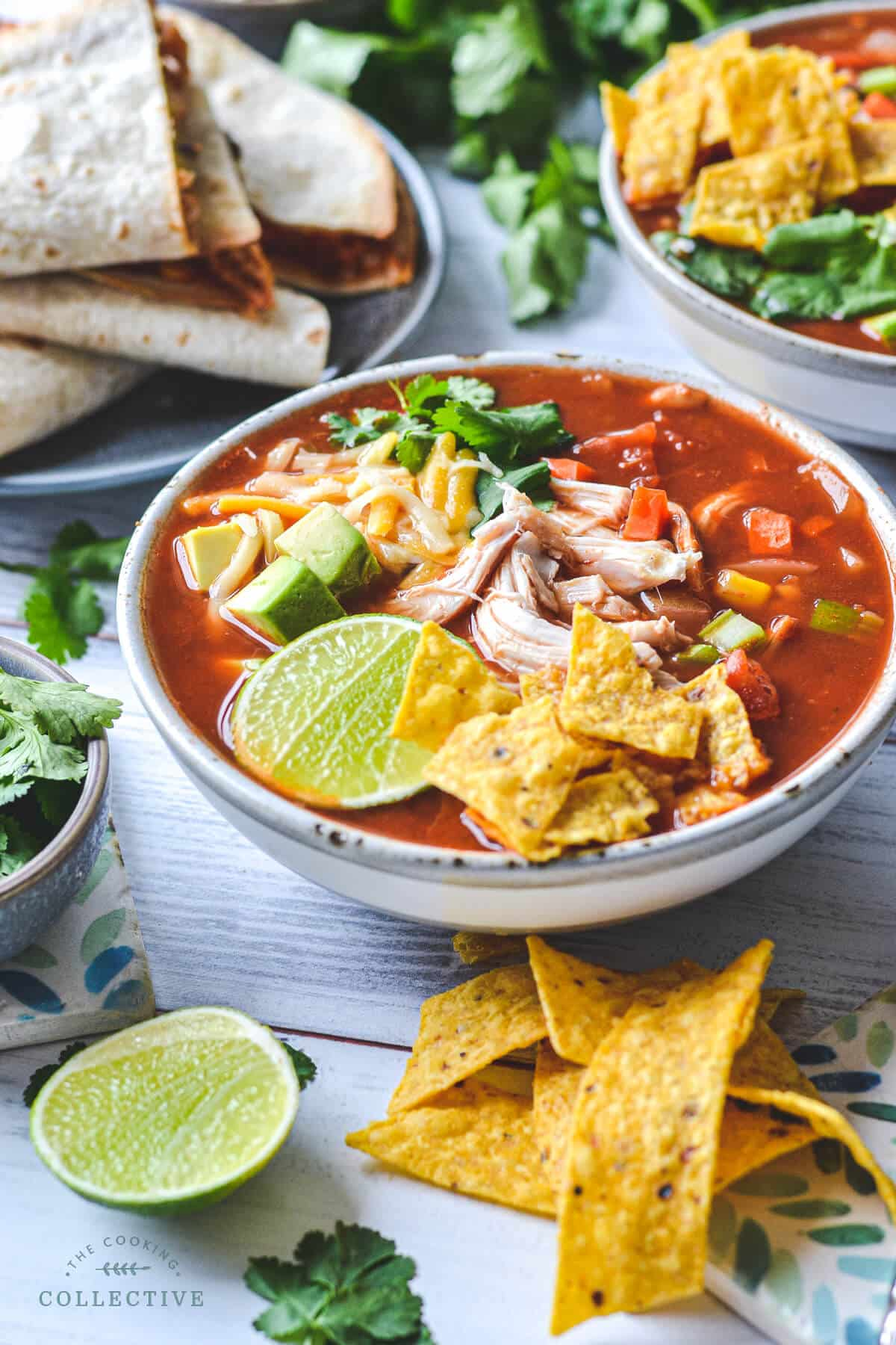 a bowl of finished soup surrounded by Mexican foods