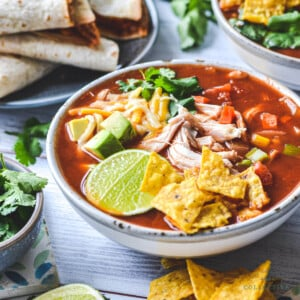 finished soup in a bowl surrounded by Mexican foods.