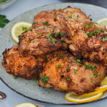air fried chicken thighs on a grey plate with lemon pieces