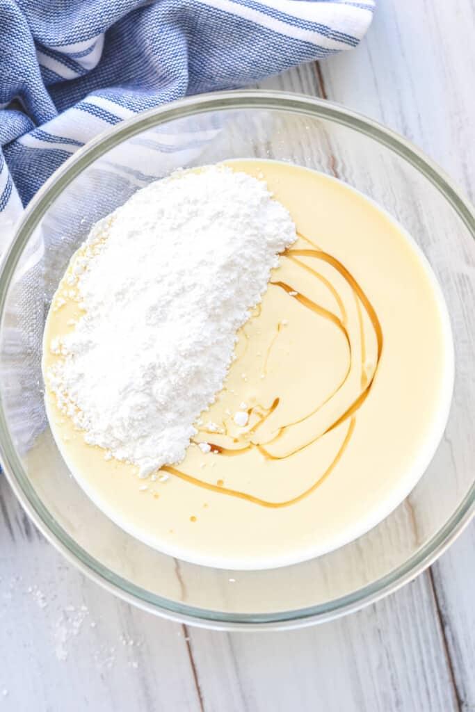 cream, icing sugar and vanilla in a glass bowl