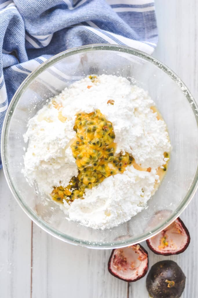 icing sugar and passion fruit pulp in a glass bowl