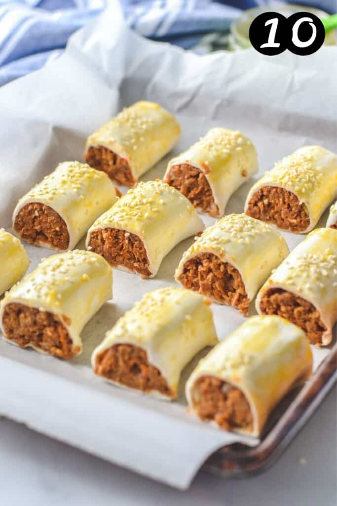 uncooked sausage rolls on a baking tray lined with paper