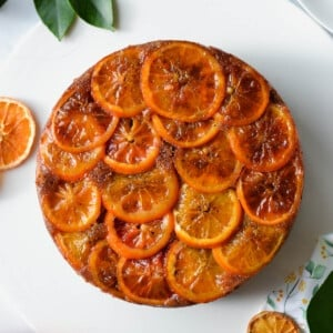top view of an orange cake covered with orange slices and syrup