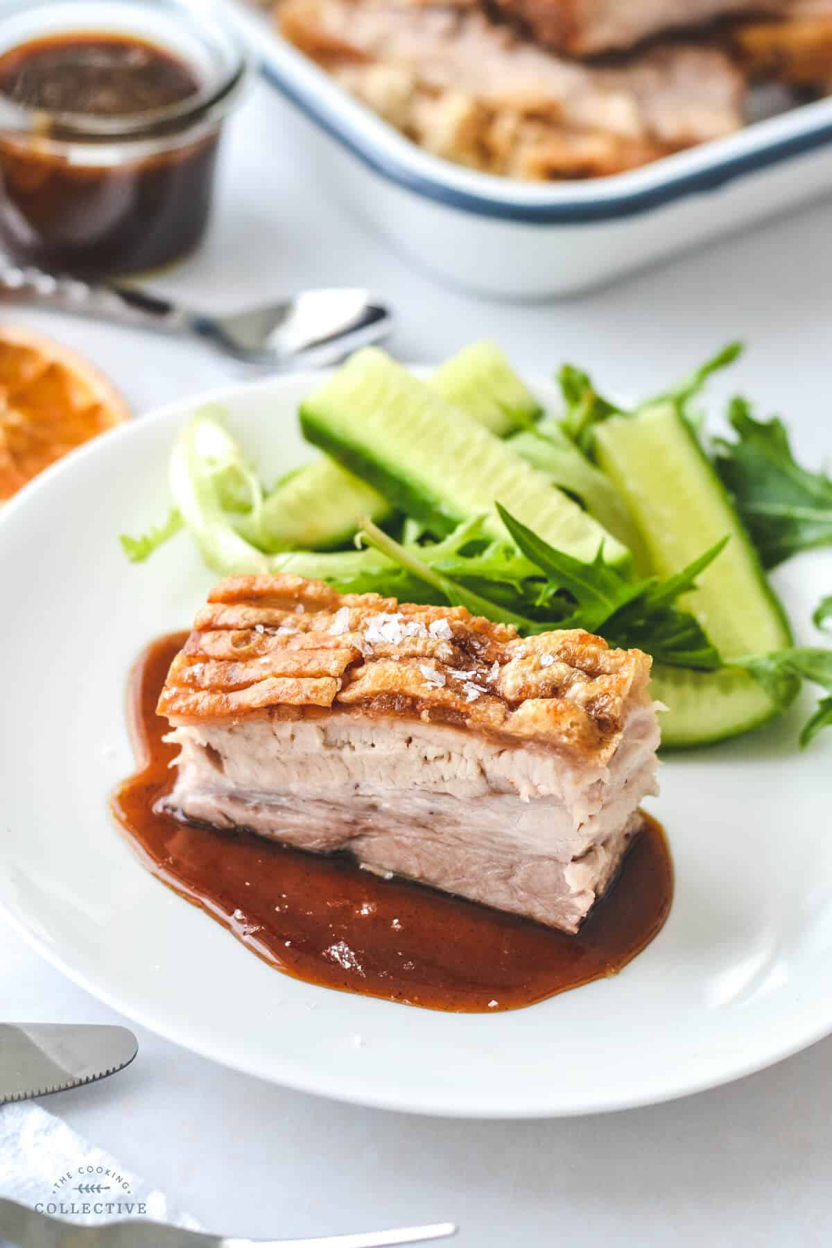 a slice of pork belly with sauce and green salad on a white plate