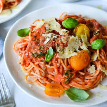 tomato pasta on a white plate topped with basil and cheese
