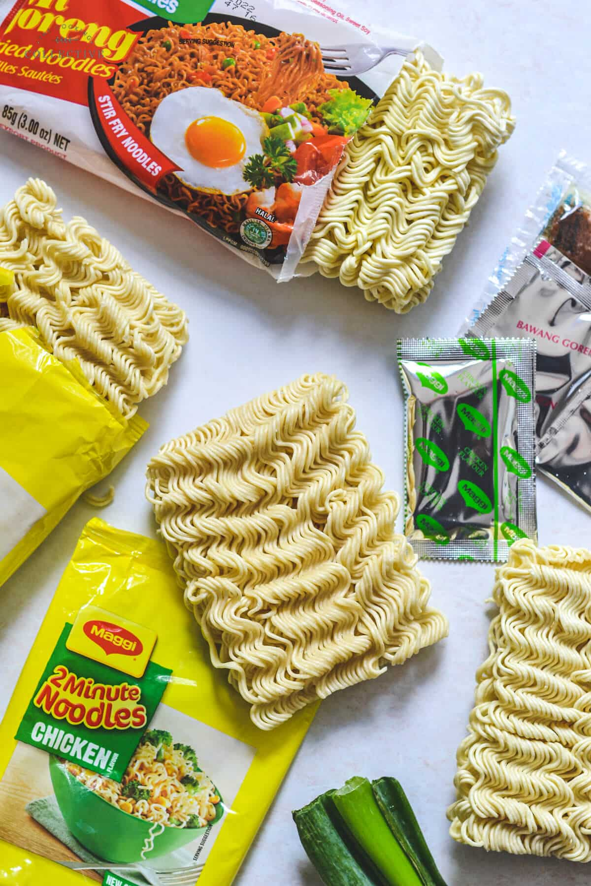 ramen noodle cakes on a white bench with seasoning packets