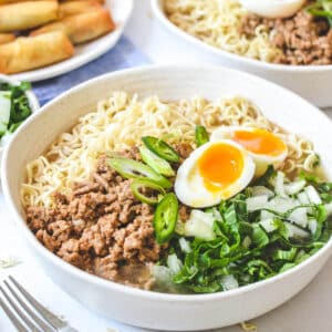 ramen soup in a bowl topped with pork, an egg and green vegetables