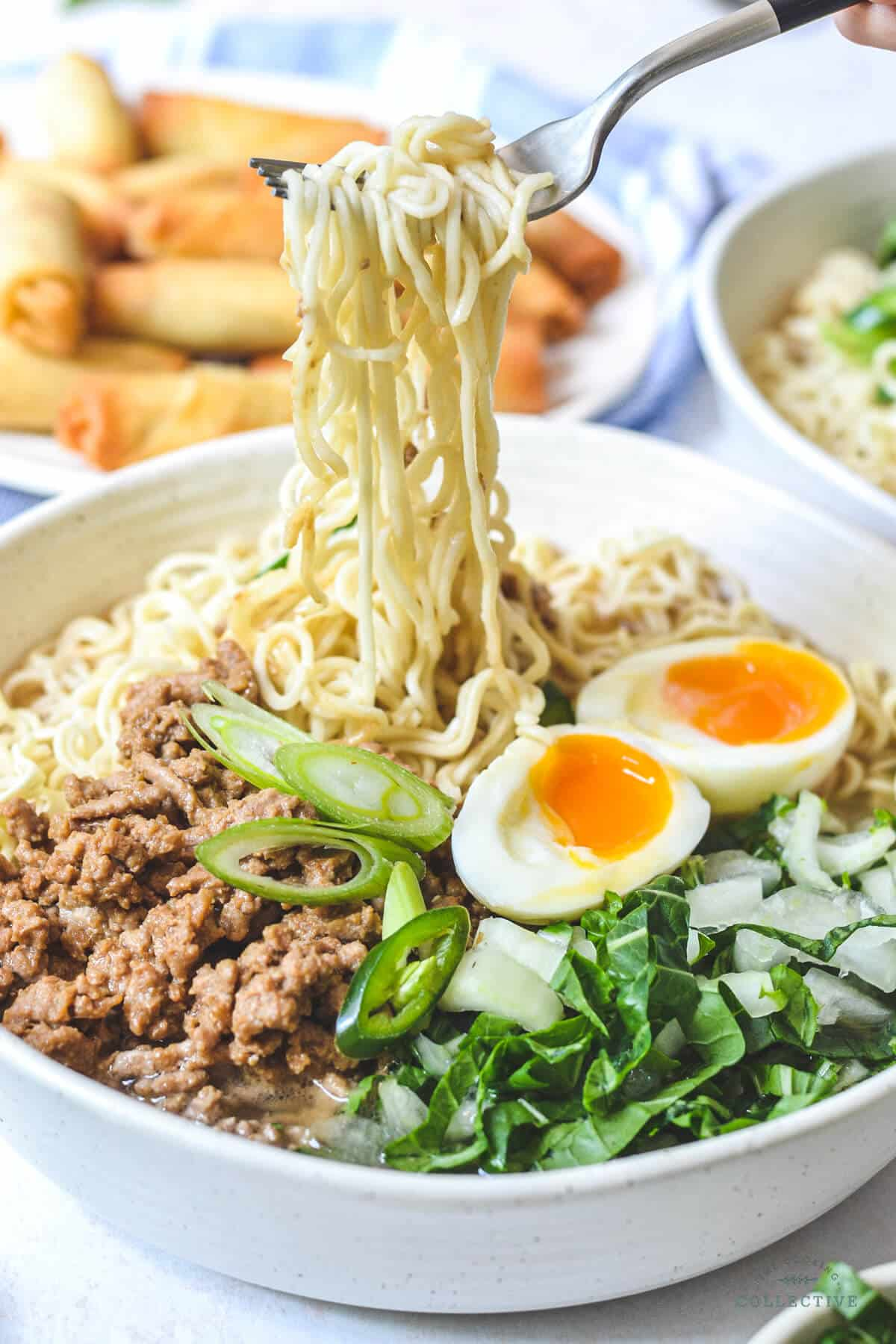 a fork holding ramen noodles above a bowl containing runny eggs, miso pork, soup and green vegetables